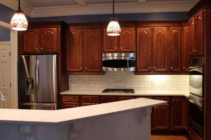 Kitchens with brown cabinets and white backsplash
